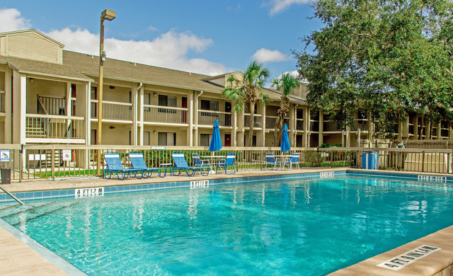Club Orlando pool with lounge chairs, tables and umbrellas for shade | Westgate Resorts in Orlando FL