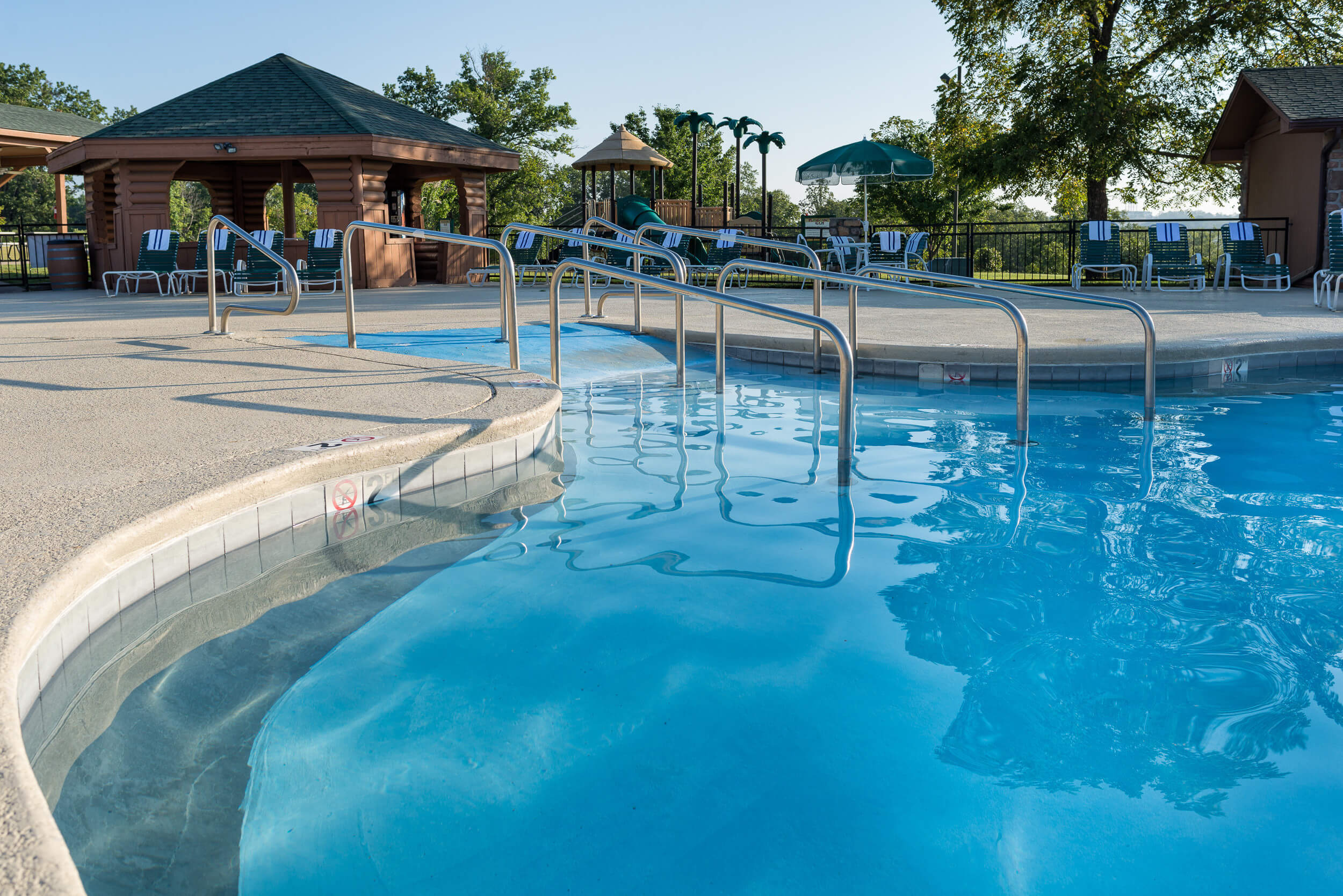 Outdoor pool surrounded by lounge chairs | Westgate Branson Woods Resort | Westgate Resorts