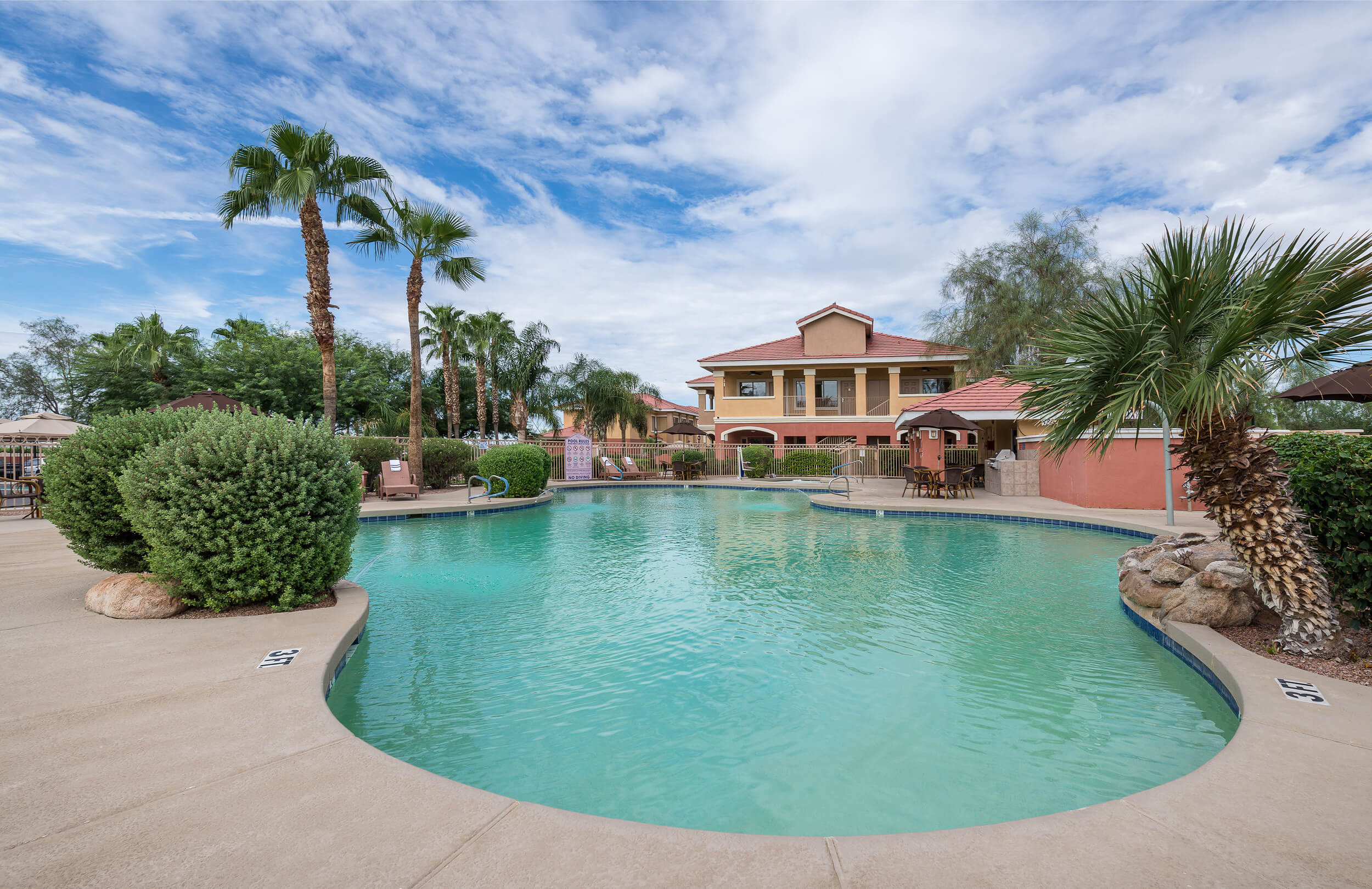 Heated outdoor pool surrounded by palm trees and landscaping | Westgate Painted Mountain Golf Resort