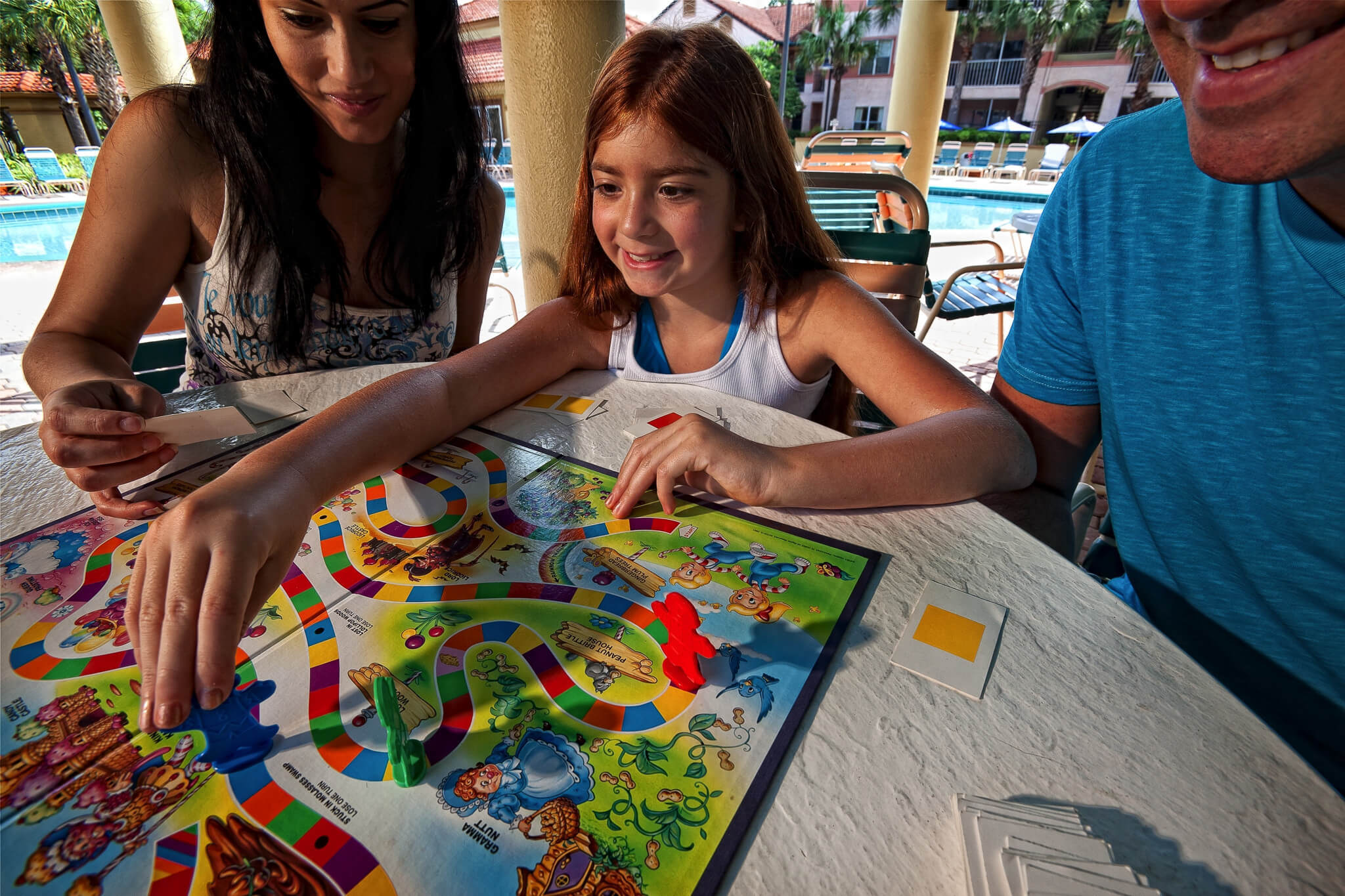 Family playing board game on pool deck | Westgate Blue Tree Resort | Westgate Resorts Orlando