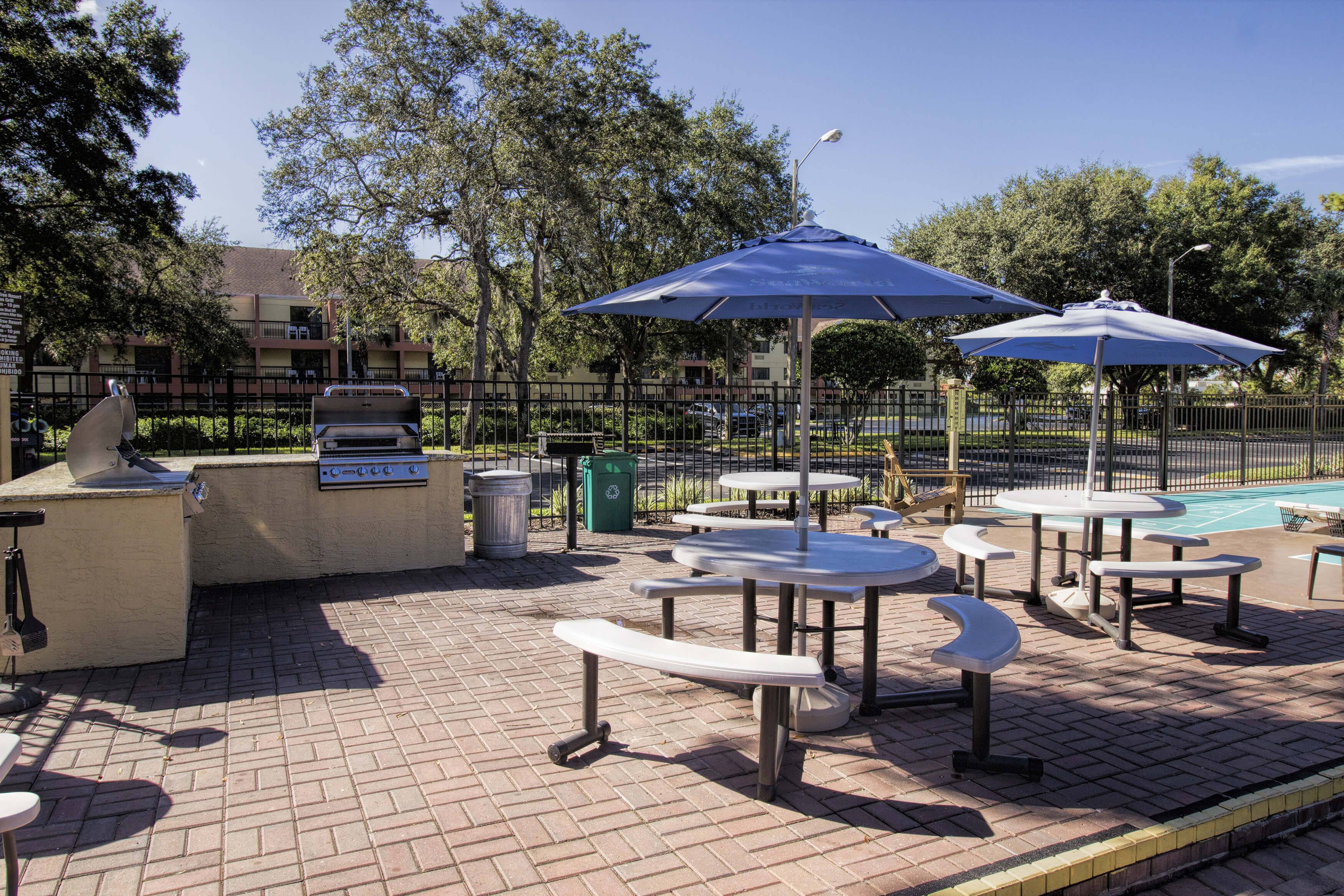Outdoor barbecue area featuring gas grills and tables with umbrellas | Westgate Blue Tree Resort
