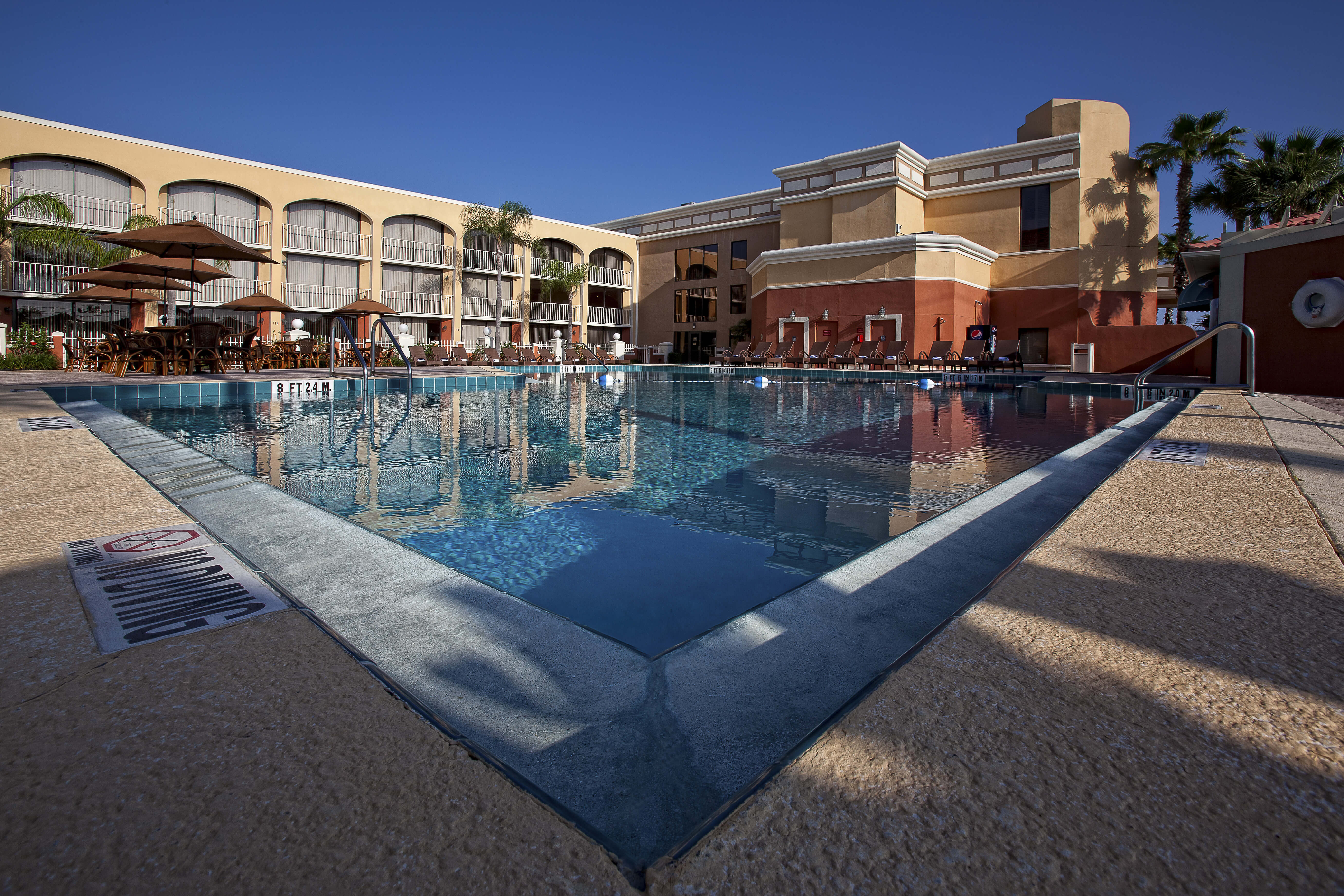 Heated outdoor pool surrounded by lounge chairs and tables with umbrellas | Westgate Towers Resort