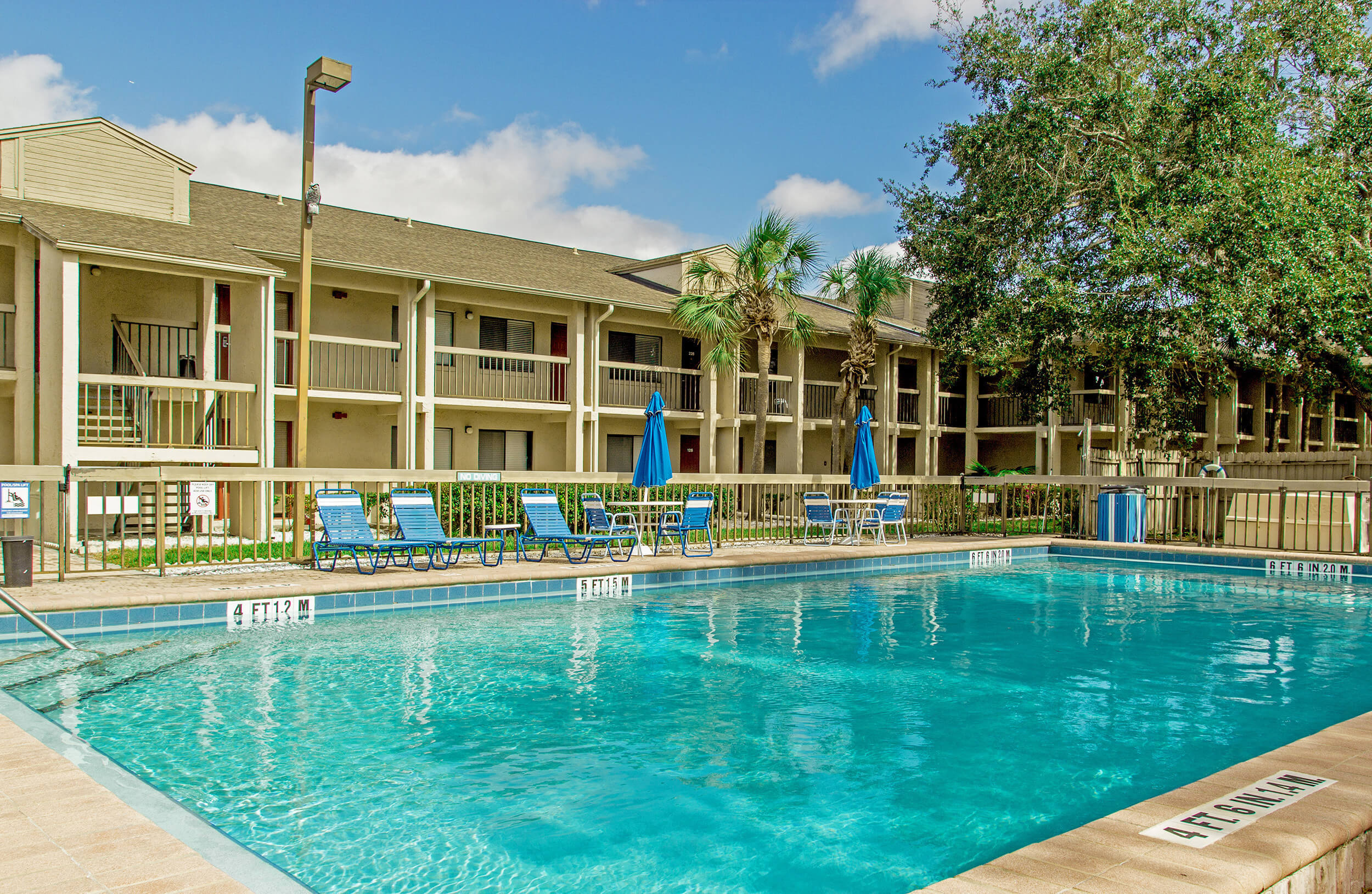 Club Orlando pool with lounge chairs, tables and umbrellas for shade | Westgate Resorts