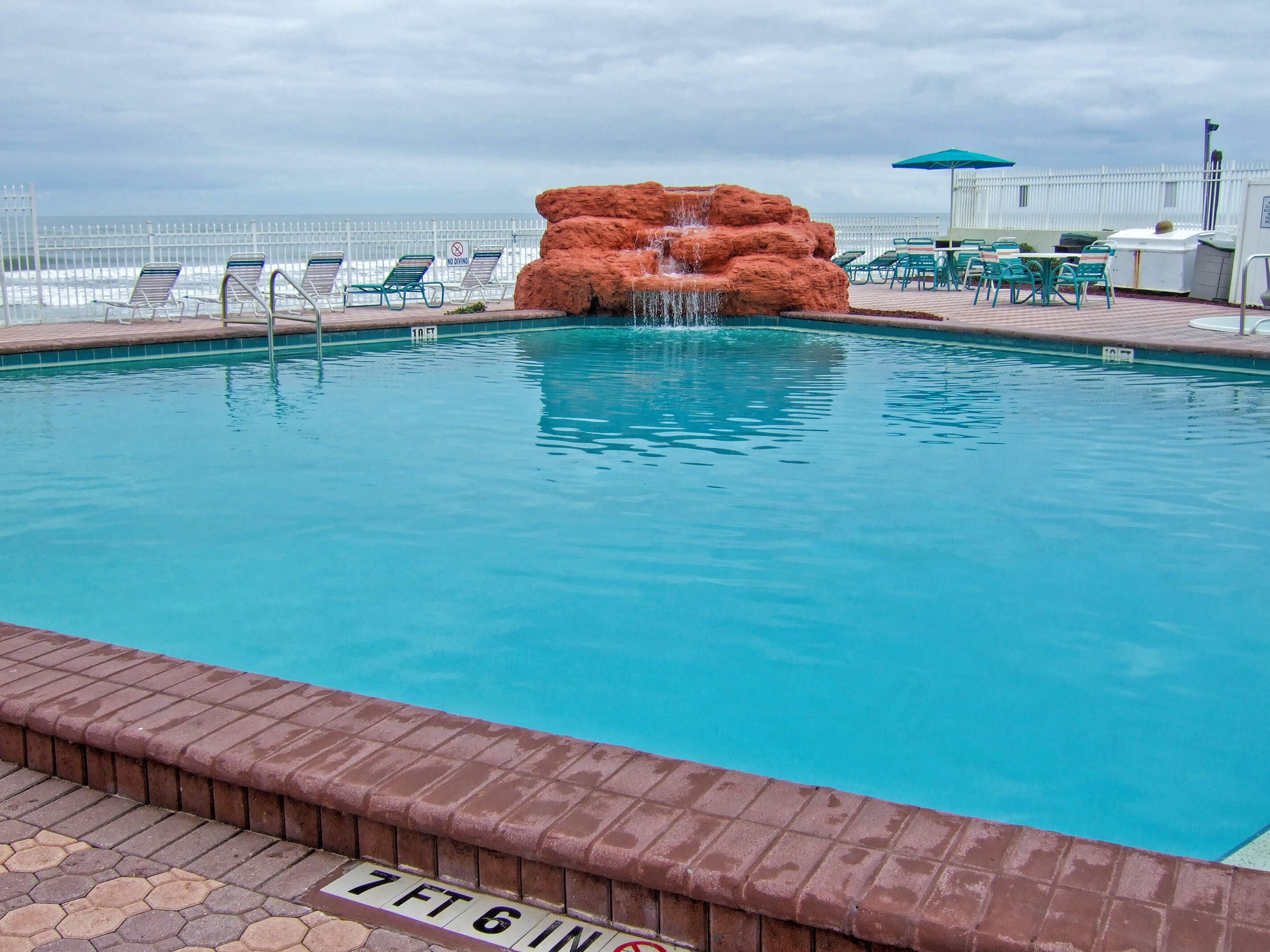 Heated outdoor pool with waterfall overlooking ocean | Harbour Beach Resort