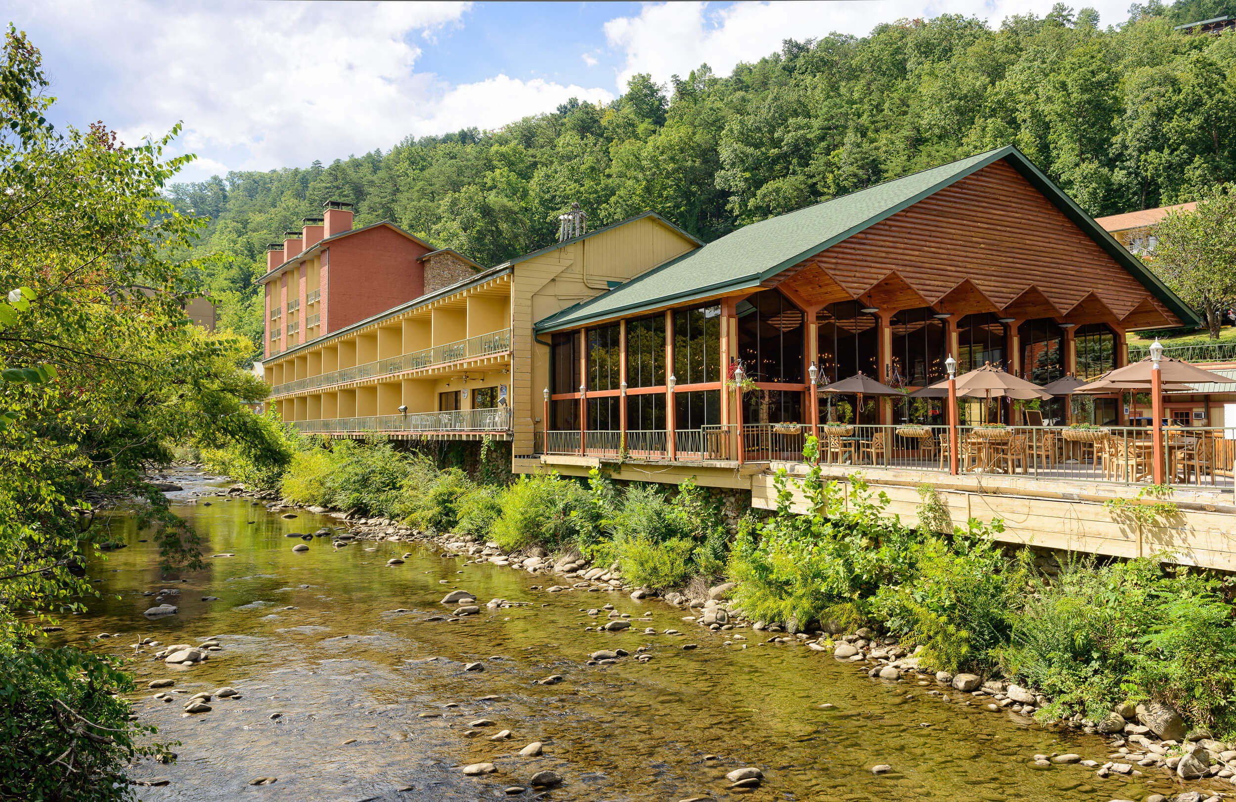 Resort exterior with onsite dining and private balconies along Little Pigeon River | River Terrace Resort & Convention Center | Westgate Resorts