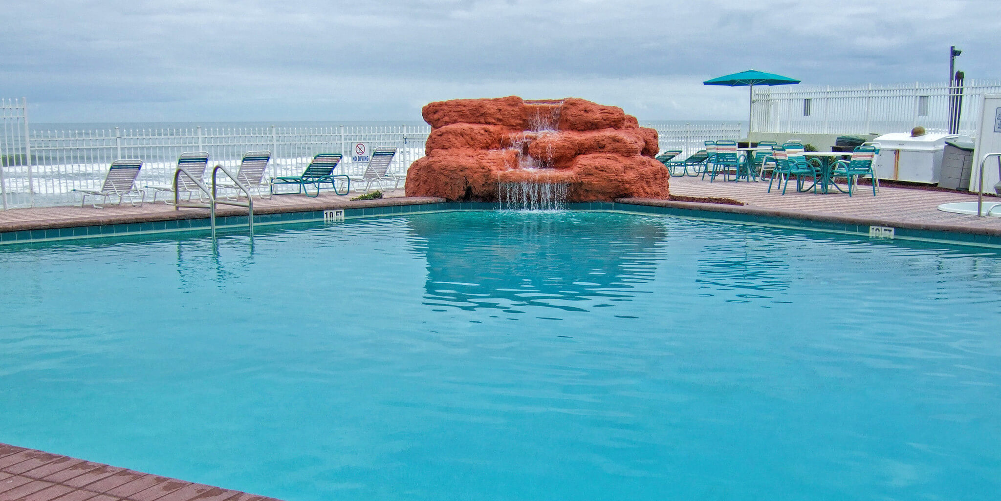Large Heated Outdoor Pool With Waterfall And Lounge Chairs Harbour Beach Resort